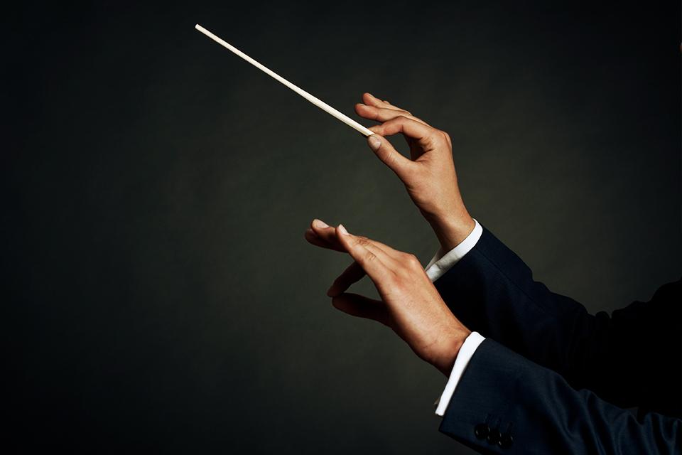 Mains de chef d'orchestre menant à la perfection un orchestre composé d'instruments variés