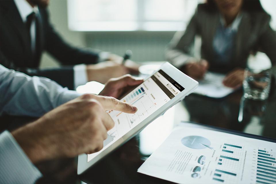 Réunion de bilan où les résultats de l'entreprise sont affichés sur tablettes
